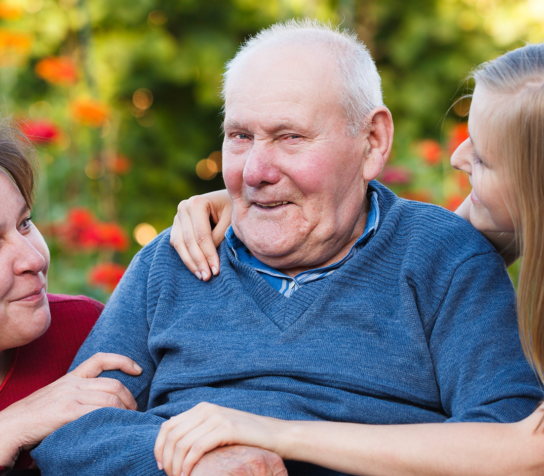 elderly man with two female carers