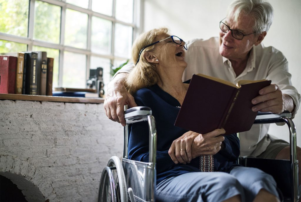 elderly woman in wheelchair reading with elderly man smiling