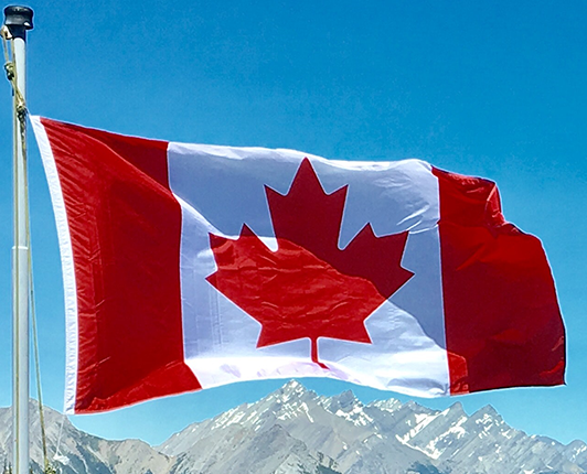 Canadian flag in front of snow-capped mountains and blue sky
