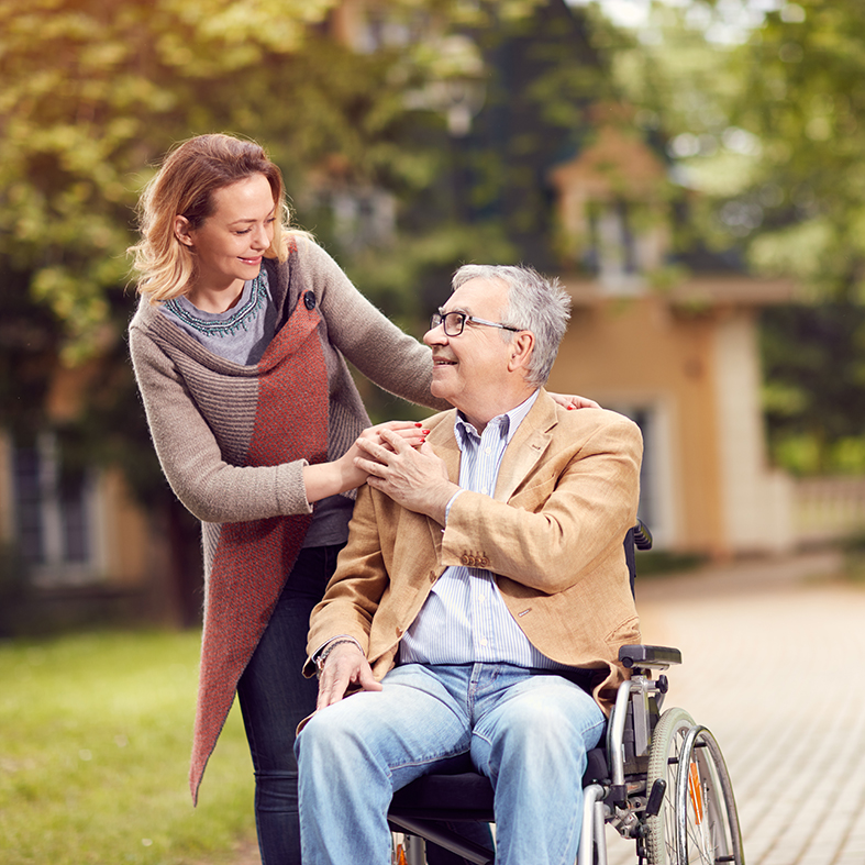 Carer smiling with person in wheelchair
