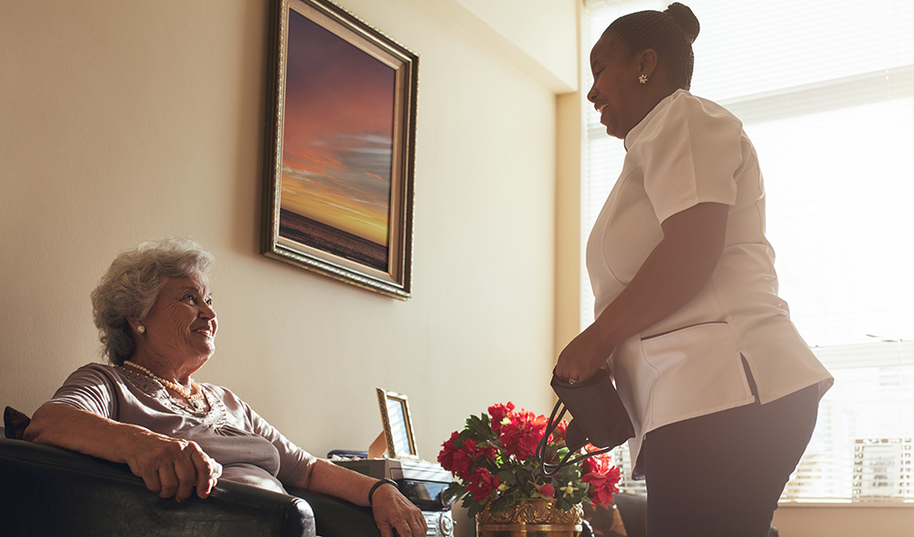 Elderly person smiling sat in chair and care worker standing smiling