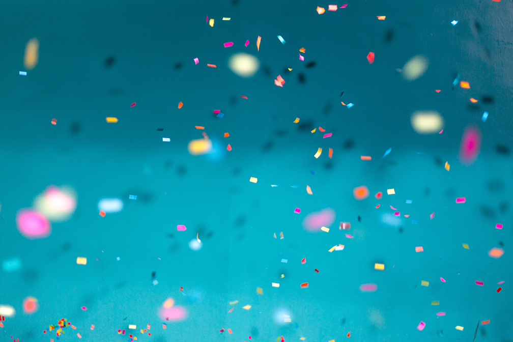 colourful confetti falling down with a teal background